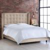 Upholstered bed with wing back headboard.
