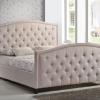 Fully upholstered bed with button tufting and nail heads with border.